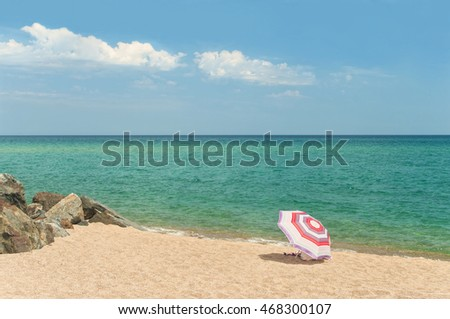 stripy colourful beach umbrella on empty sandy beach with big rocks and beautiful turquoise water of Mediterranean sea, Santa Susanna, Catalonia, Spain