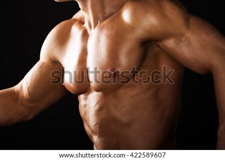Strong Athletic Man showing muscular body black background.Muscular bodybuilder runing black background.Muscular man on black background