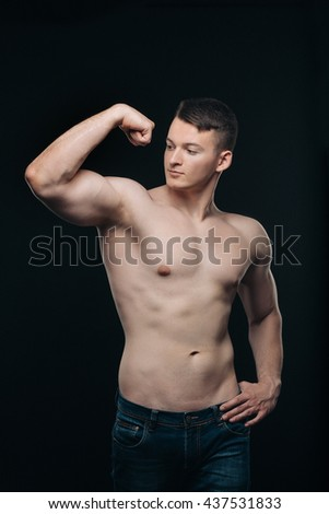 Strong athletic young  man on black