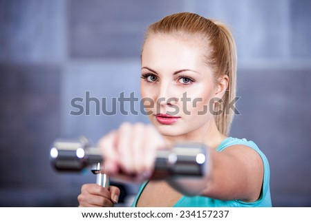 Strong blonde woman weightlifting at the gym, doing shoulders exercise