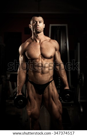 Strong bodybuilder with dumbbells in the gym
