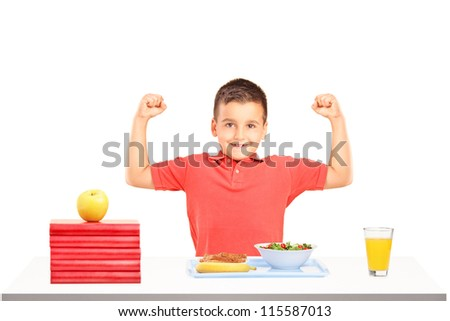 Strong boy showing his muscles and food on table during a breakfast isolated on white background