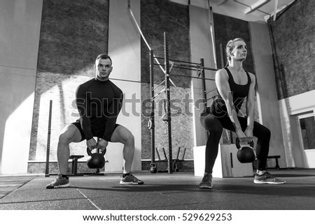 Strong well built man and woman holding kettlebells