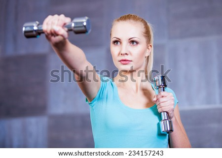 Strong young woman exercising with dumbbells at the gym doing shoulder muscles exercise