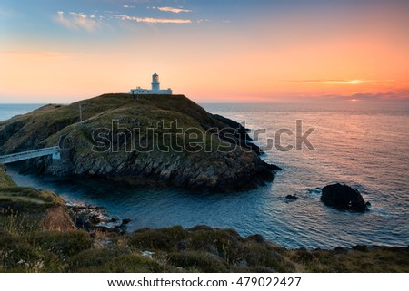 Strumble Head Lighthouse at sunset . It stands on a rocky island along Pembrokeshire coast, Wales