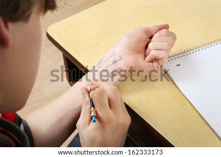Student cheating writing answers on arm
