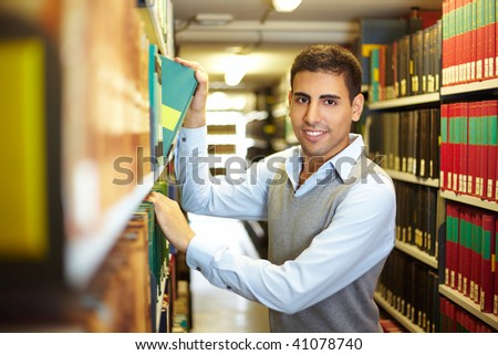 Student looking for a book in library archive