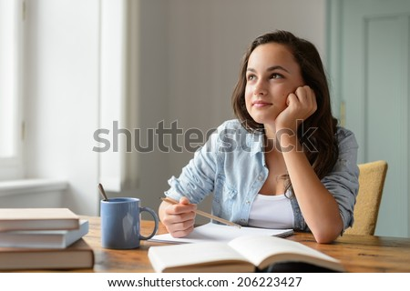 Student teenage girl studying at home daydreaming looking away