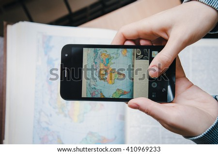 Student young woman taking a photo world map image book on screen black with Smartphone. Top view. Female hand holding and touch mobile phone in library textbook. Modern life concept. Film color