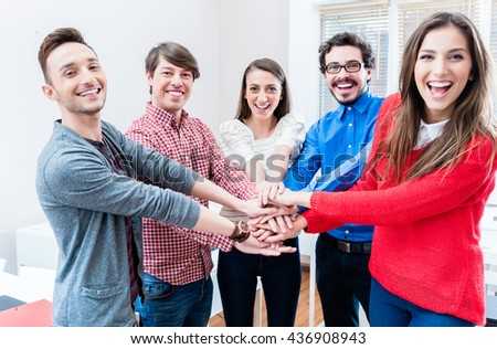 Students in university or college cling together stacking hands as a team