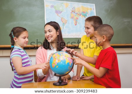 Students pointing to places on a globe at the elementary school