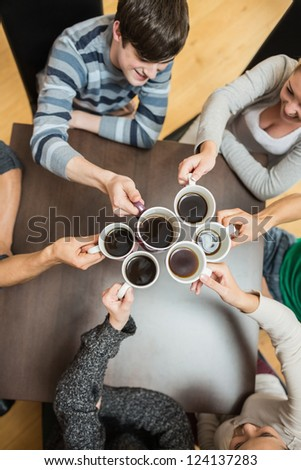 Students sitting holding cups of coffee smiling in college cafe