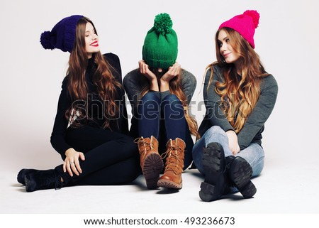 Studio fashion portrait of a group of three young beautiful model posing in winter leather shoes, warm clothes and colorful knitted caps. Friends having fun. Consumer concept, winter fashion