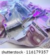 studio photography of crumbled euro banknotes illuminated with colored light - stock photo