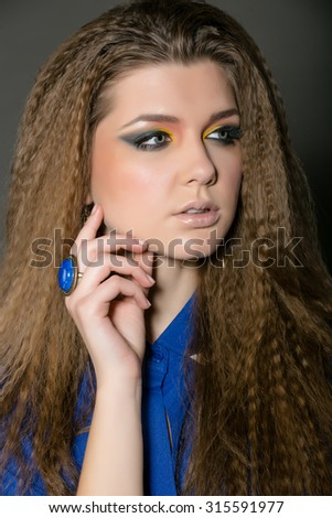 Studio photos sexy girl with stylish make-up in a blue shirt against a dark background