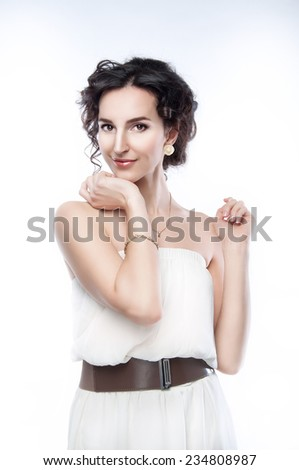 Studio portrait of a beautiful brunette with evening hairdo and makeup on white background