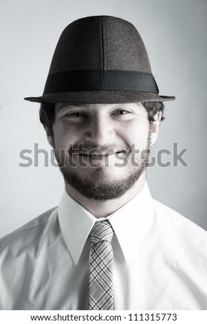 Studio portrait of a college boy wearing a hat and tie smiling to the camera