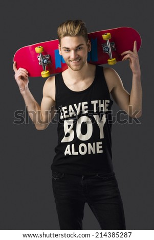 Studio portrait of a young man posing with a skateboard