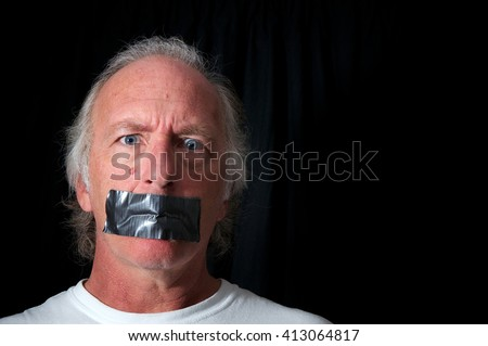 Studio portrait of an older blue eyed man with mouth duct taped closed, looking distraught, black background with copy space. Political correctness or freedom of speech concept.