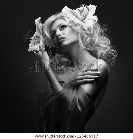 studio portrait of beautiful blonde with wide opened eyes wearing flowers in her hair and tropical butterfly sitting on her hand on dark background