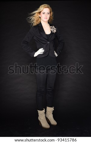Studio portrait of pretty young woman with pink lipstick and long blond hair. Wearing a black suit and white gloves. Isolated on black background.