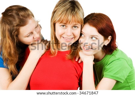 Studio portrait of three friendly girls close together in a hug, isolated on a white background.