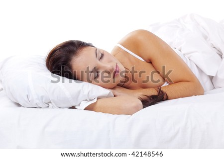 Studio portrait of young beautiful woman on bed
