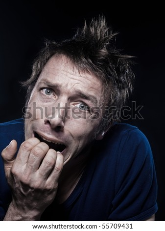 studio portrait on black background of a funny expressive caucasian man grimacing fear