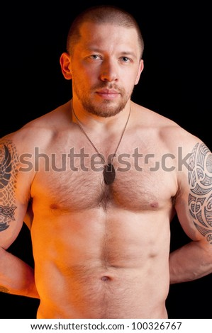 Studio shot of a brawny caucasian male with bare torso wearing dog tags