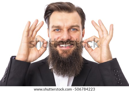Studio shot of a happy elegant man with beard and mustache