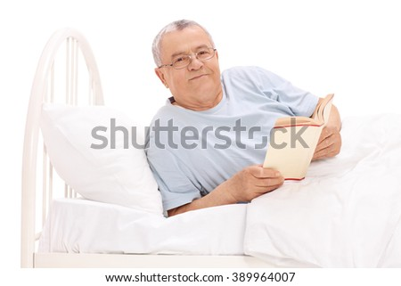 Studio shot of a relaxed senior man lying in bed and holding a book isolated on white background