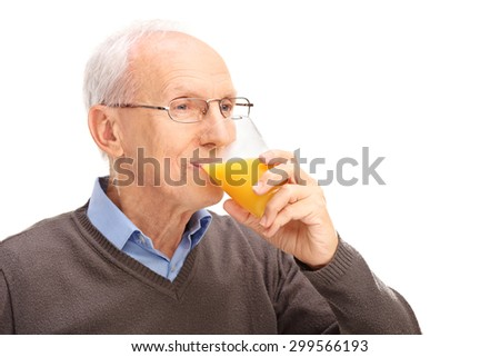 Studio shot of a senior drinking an orange juice isolated on white background