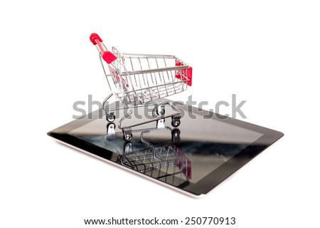 Studio shot of a shopping cart over a tablet computer