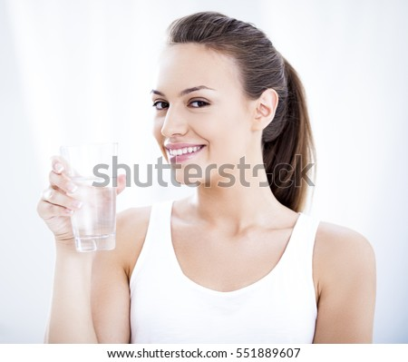 Studio shot of a young woman holding a glass of water.