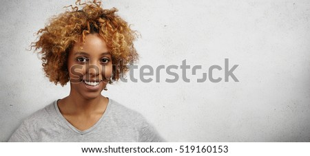 Studio shot of beautiful young African girl with dyed curly hair wearing gray t-shirt looking and smiling at camera with joyful expression while standing against copy space wall for your advertisement