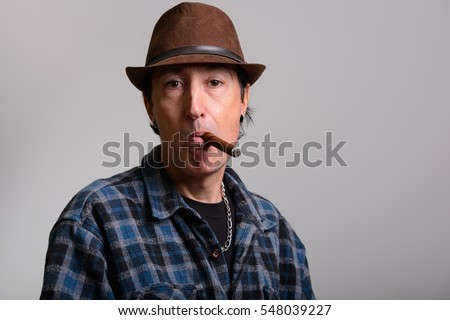 Studio shot of mature gangster man smoking cigar