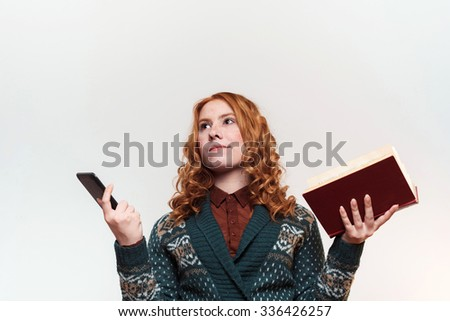 studio shot of redhead girl with ebook and book on white background. Old vs modern. Education concept