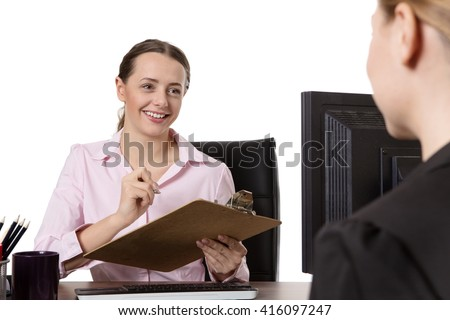 Studio shot of two happy coworkers enjoying a conversation whilst sitting at a desk.  One lady is holding a clipboard.