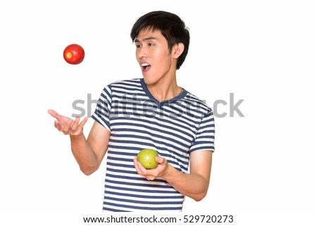 Studio shot of young handsome Asian man holding apple isolated against white background