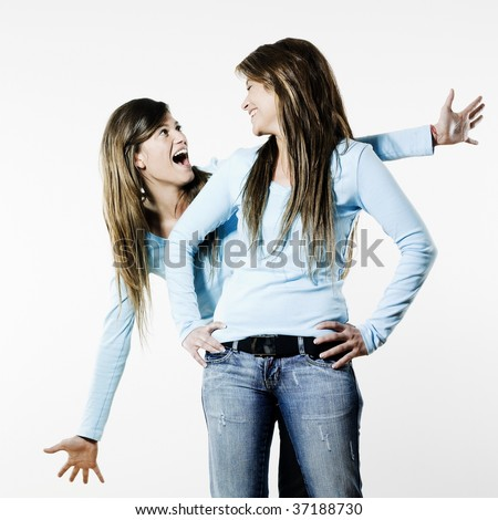 studio shot portrait on isolated background of two sisters twin women friends one raising from the back of the other