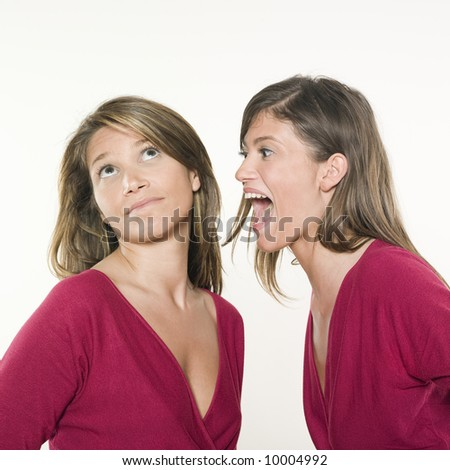 studio shot portrait on isolated background of two sisters twin women friends one screaming the other is not listening
