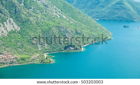 Stunning landscape of famous and beautiful Boka bay in Montenegro. Azure water surrounded by green mountains with red mediterranean houses on it.