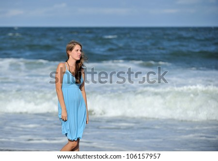 Stunning young Caucasian woman standing on a beach in a blue sun dress - looking off frame as waves roll in behind her