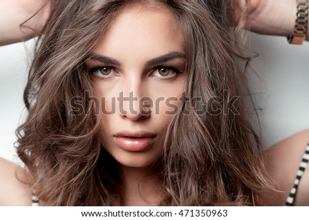 Stunning young woman with curly hair, portrait