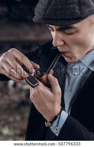 stylish gangster man, smoking, lighting wooden pipe. posing on background of railway. england in 1920s theme. fashionable brutal confident guy. atmospheric  moments.