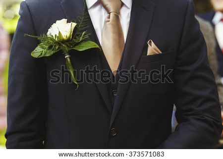 Stylish groom in dark suit with white rose in buttonhole