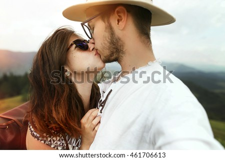 stylish hipster couple kissing top of mountains in summer, travel together concept, space for text, romantic perfect moment