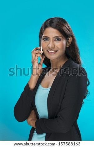 Stylish Indian Woman using a smart phone. Young and fresh Asian female model a bright blue background.
