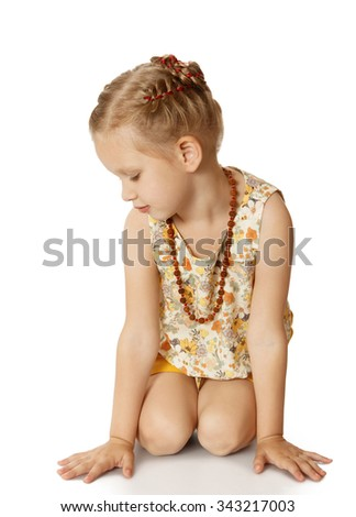 Stylish little blonde girl in shorts and sleeveless t-shirt is sitting on the floor . On the neck of the girl beautiful large beads - Isolated on white background