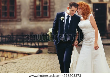 stylish luxury red haired bride and elegant groom, walking on the background of the old city Lviv